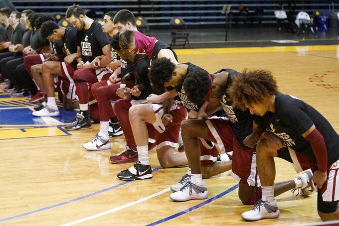 Washington State players kneel during the national anthem before an NCAA college basketball game against Stanford in Santa Cruz, Calif., Saturday, Jan. 9, 2021. (AP Photo/Jeff Chiu)