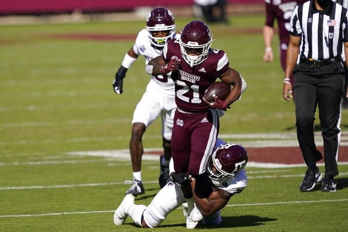 Mississippi State running back Jo'quavious Marks (21) runs for a first down as he is tackled by a Texas A&M defender during the first half of an NCAA college football game in Starkville, Miss., Saturday, Oct. 17, 2020. (AP Photo/Rogelio V. Solis)