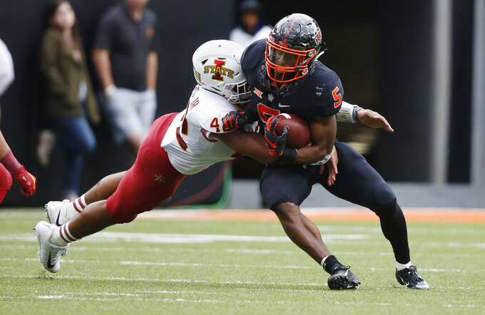 Oklahoma State running back Justice Hill (5) is tackled by Iowa State linebacker Marcel Spears Jr. (42) in the second half of an NCAA college football game in Stillwater, Okla., Saturday, Oct. 6, 2018. (AP Photo/Sue Ogrocki)