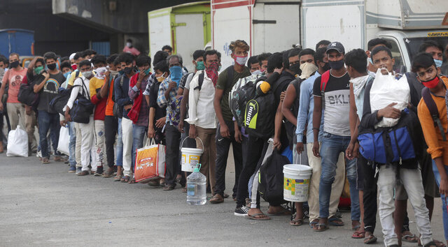 Migrant workers from other states wait in queues outside a railway station to catch a train to return to their homes, in Mumbai, India, Friday, May 15, 2020. The pandemic has exposed India's deep economic divide as millions of migrant workers have left Indian cities with luggage bags perched on their heads and children in their arms, walking down highways in desperate attempts to reach the countryside. (AP Photo/Rafiq Maqbool)