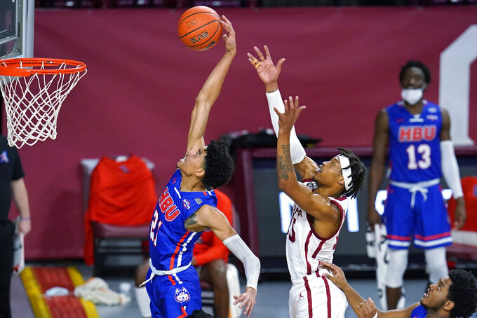 Houston Baptist guard Pedro Castro, left, reaches for a rebound in front of Oklahoma guard Alondes Williams, right, in the second half of an NCAA college basketball game Saturday, Dec. 19, 2020, in Norman, Okla. (AP Photo/Sue Ogrocki)