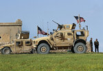 FILE - In this file picture taken on Thursday, March 29, 2018, a fighter, second from right, of U.S-backed Syrian Manbij Military Council stands next to U.S. humvee at a U.S. troop's outpost on a road leading to the tense front line between Syrian Manbij Military Council fighters and Turkish-backed fighters, at Halawanji village, north of Manbij, Syria.    A spokesman for the U.S.-led coalition said Friday, Jan. 11, 2019 that the process of withdrawal in Syria has begun, declining to comment on specific timetables or movements. (AP Photo/Hussein Malla, File)