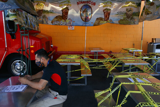 FILE - In this July 1, 2020, file photo, Abel Gomez waits for his order at Mariscos Linda food truck as dining tables are sealed off with caution tape due to the coronavirus pandemic in Los Angeles. California Gov. Gavin Newsom has extended the closure of bars and indoor dining statewide and has ordered gyms, churches and hair salons closed in most places as coronavirus cases keep rising. On Monday, July 13, 2020, Newsom extended that order statewide and closed additional parts of the world's fifth-largest economy, including indoor malls and offices for noncritical industries. (AP Photo/Jae C. Hong, File)