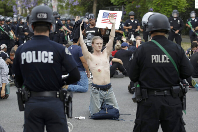 FILE - In this June 1, 2020, file photo, a protester raises his arm shortly before being arrested for violating a curfew in the Hollywood area of Los Angeles. Two reviews of the violence that surrounded last summer's police brutality protests in Los Angeles say the LAPD wasn't prepared to react when peaceful demonstrations were marred by clashes, vandalism and looting. The Los Angeles Times says the reports, released Friday, April 9, 2021 found that poor planning, inconsistent leadership and inadequate training contributed to disorder in the streets that caused an estimated $167 million in losses to private property and businesses owners. (AP Photo/Marcio Jose Sanchez, File)