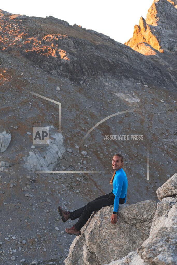 Smiling female tourist sitting on rock, Picos de Europe, Cantabria, Spain