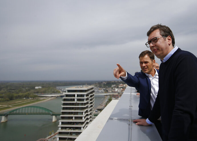 In this Friday, April 5, 2019, photo, Serbia's finance minister Sinisa Mali, left, speaks with Serbia's President Aleksandar Vucic in Belgrade, Serbia. Serbia's finance ministry has launched an investigation into money laundering and financing of terrorism against dozens of rights organizations, independent journalists and opposition politicians who have been exposing alleged government corruption. (AP Photo/Darko Vojinovic)