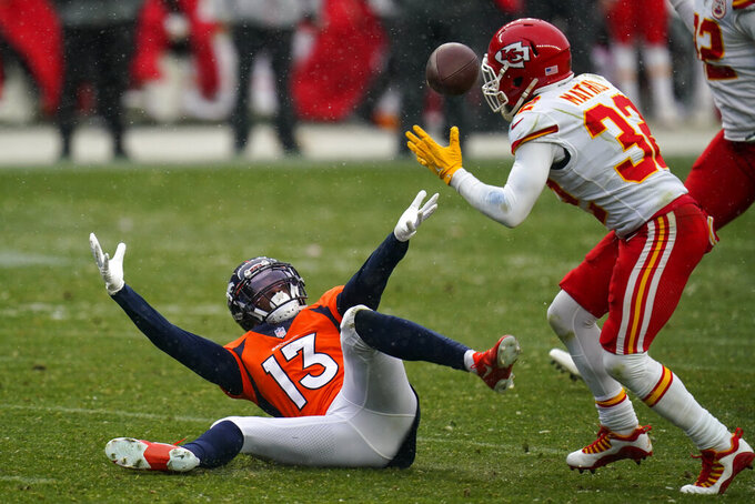 Denver Broncos wide receiver K.J. Hamler (13) falls as Kansas City Chiefs strong safety Tyrann Mathieu intercepts a pass during the second half of an NFL football game Sunday, Oct. 25, 2020, in Denver. (AP Photo/Jack Dempsey)