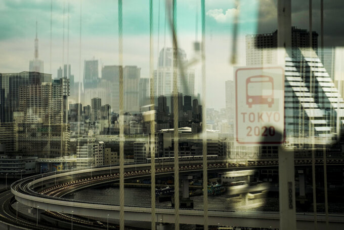 The skyline of Tokyo is seen through a bus window from the Rainbow Bridge ahead of the 2020 Summer Olympics, Wednesday, July 14, 2021, in Tokyo. (AP Photo/Jae C. Hong)
