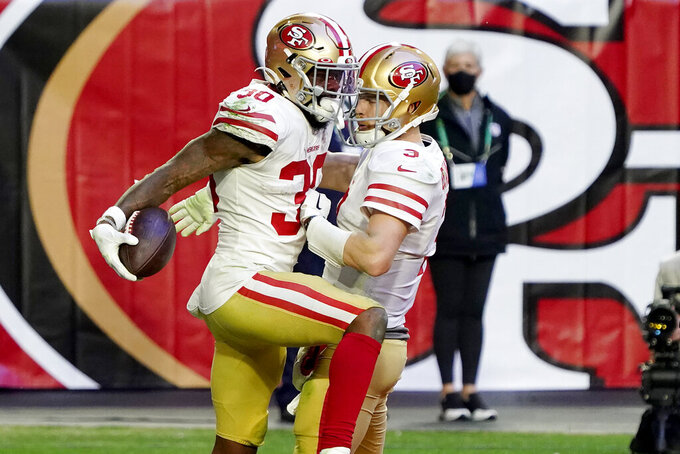 San Francisco 49ers running back Jeff Wilson (30) celebrates his touchdown with quarterback C.J. Beathard (3) during the second half of an NFL football game against the Seattle Seahawks, Sunday, Jan. 3, 2021, in Glendale, Ariz. (AP Photo/Rick Scuteri)