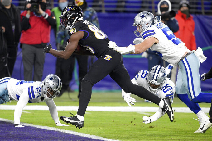 Baltimore Ravens wide receiver Miles Boykin, center, scores a touchdown on a pass from quarterback Lamar Jackson, not visible, as Dallas Cowboys outside linebacker Leighton Vander Esch (55), free safety Xavier Woods (25) and cornerback Chidobe Awuzie (24) try to stop him during the first half of an NFL football game, Tuesday, Dec. 8, 2020, in Baltimore. (AP Photo/Nick Wass)