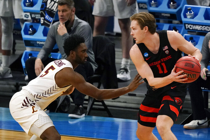Oregon State guard Zach Reichle (11) looks to drive around Loyola Chicago guard Keith Clemons (5) during the first half of a Sweet 16 game in the NCAA men's college basketball tournament at Bankers Life Fieldhouse, Saturday, March 27, 2021, in Indianapolis. (AP Photo/Jeff Roberson)