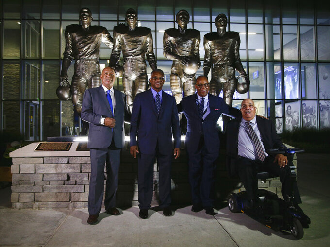 FILE - In this Sept. 22, 2016, file photo, from left, Mel Page, representing his brother Greg Page; Nate Northington; Wilbur Hackett; and Houston Hogg pose after statues of them were unveiled at the University of Kentucky in Lexington. Houston Hogg, one of four African-American football players at Kentucky who helped break the Southeastern Conference color line in the late 1960s, has died. He was 71. The school announced Friday, Jan. 3, 2020, that Hogg died in Owensboro, Kentucky.  (Mark Cornelison/Lexington Herald-Leader via AP, File)