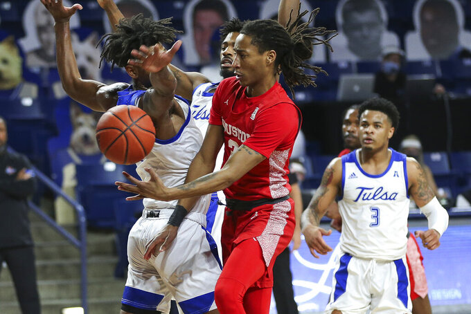 Houston's DeJon Jarreau drives to the basket against Tulsa defenders during the first half of an NCAA college basketball game in Tulsa, Okla., Tuesday, Dec. 29, 2020. (AP Photo/Dave Crenshaw)
