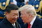 FILE - In this Nov. 9, 2017, file photo, U.S. President Donald Trump, right, chats with Chinese President Xi Jinping during a welcome ceremony at the Great Hall of the People in Beijing. China said Friday, Oct. 12, 2018 it is in contact with the United States amid reports of a planned meeting between President Xi Jinping and President Donald Trump next month following a dive in the U.S. stock market blamed partly on a growing trade war between the world's two largest economies. (AP Photo/Andy Wong, File)