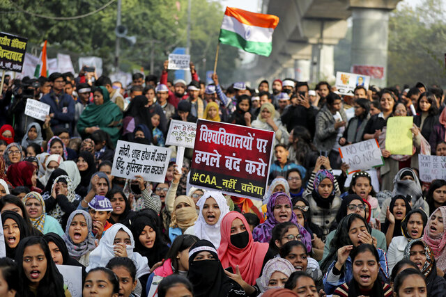 Indian students of the Jamia Millia Islamia University and locals participate in a protest demonstration against a new citizenship law in New Delhi, India, Saturday, Dec. 21, 2019. Critics have slammed the law as a violation of India's secular constitution and have called it the latest effort by the Narendra Modi government to marginalize the country's 200 million Muslims. Modi has defended the law as a humanitarian gesture. Placard center reads