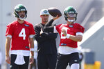 New York Jets quarterback Zach Wilson (2) looks to pass as James Morgan (4) and quarterbacks coach Rob Calabrese look on during practice at the team's NFL football training facility, Saturday, July. 31, 2021, in Florham Park, N.J. (AP Photo/Rich Schultz)