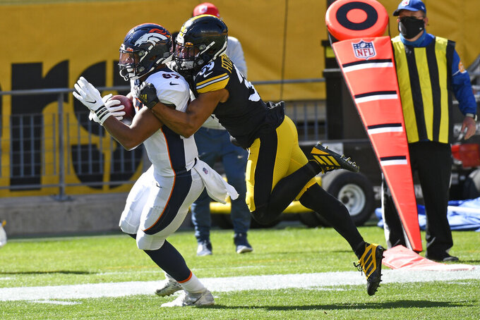 Denver Broncos tight end Noah Fant, left,  is tackled by Pittsburgh Steelers free safety Minkah Fitzpatrick, right, during the second half of an NFL football game in Pittsburgh, Sunday, Sept. 20, 2020. (AP Photo/Don Wright)