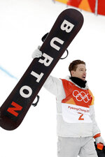 FILE - In this Feb. 14, 2018, file photo, Shaun White, of the United States, holds up his Burton snowboard as he celebrates his run during the men's halfpipe finals at the 2018 Winter Olympics in Pyeongchang, South Korea. Jake Burton Carpenter, the man who changed the game on the mountain by fulfilling a grand vision of what a snowboard could be, died Wednesday night, Nov. 20, 2019,  of complications stemming from a relapse of testicular cancer. He was 65. (AP Photo/Gregory Bull, File)