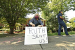 A protesters sits outside the house of Senate Majority Leader Mitch McConnell, R-Ky., in Louisville, Ky., Saturday, Sept. 19, 2020. McConnell vowed on Friday night, hours after the death of Supreme Court Justice Ruth Bader Ginsburg to call a vote for whomever President Donald Trump nominated as her replacement. (AP Photo/Timothy D. Easley)