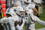 Miami Dolphins tight end Mike Gesicki, center, celebrates with teammates after scoring a touchdown on a 15-yard pass play against the Jacksonville Jaguars during the first half of an NFL football game, Thursday, Sept. 24, 2020, in Jacksonville, Fla. (AP Photo/Stephen B. Morton)