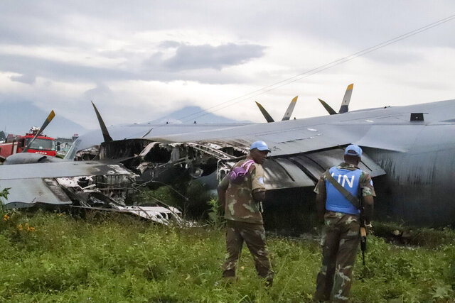 United Nations personnel attend the scene where a South African air force plane crash-landed and caught fire at the airport in Goma, eastern Congo Thursday, Jan. 9, 2020. The C-130BZ military aircraft was transporting 59 passengers and eight crew members from the U.N mission when its left engine caught fire upon landing, according to the U.N. peacekeeping mission known as MONUSCO, and there were no casualties, authorities said. (AP Photo/Justin Kabumba)