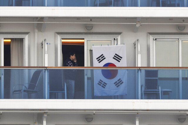 In this Feb. 15, 2020, photo, a man talks on the phone next to a South Korean flag hanging in the balcony of his cabin on the quarantined Diamond Princess cruise ship in Yokohama, near Tokyo. The 14-day quarantine for those on the ship is scheduled to end Wednesday. (AP Photo/Jae C. Hong)