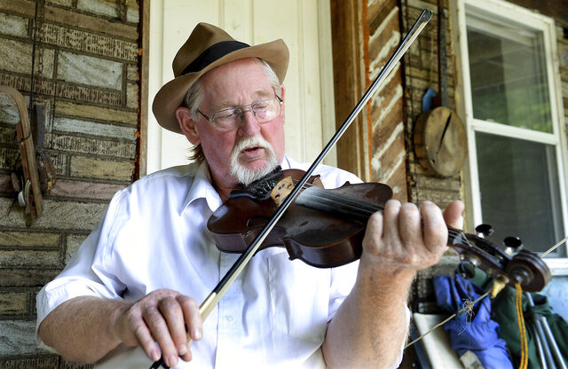 John Morris plays his fiddle on his porch at his house in Clay County, W.Va., Thursday, July 2, 2020. (Chris Dorst/Charleston Gazette-Mail via AP)