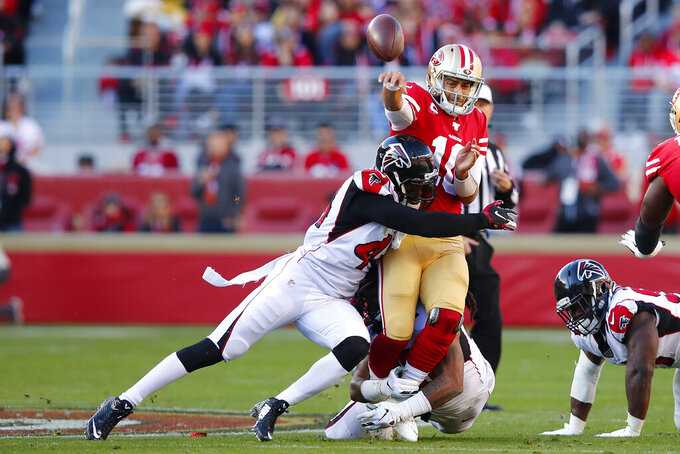 San Francisco 49ers quarterback Jimmy Garoppolo, top, is hit while passing by Atlanta Falcons defensive end Vic Beasley, left, and defensive end Adrian Clayborn, bottom center, during the first half of an NFL football game in Santa Clara, Calif., Sunday, Dec. 15, 2019. (AP Photo/John Hefti)