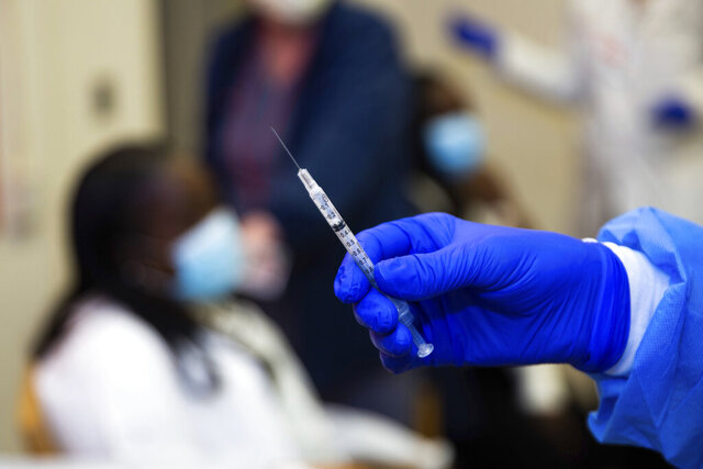 A doctor prepares to administer a vaccine injection to Claudia Scott-Mighty, a patient care director at NewYork-Presbyterian Lawrence Hospital on Friday, Jan. 8, 2021, in Bronxville, N.Y. The second round of the vaccine increases its efficacy to 95%, according to Pfizer. (AP Photo/Kevin Hagen).
