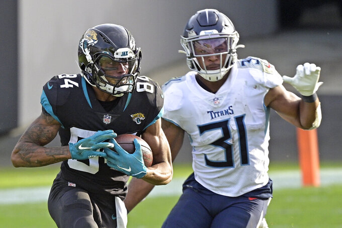 Jacksonville Jaguars wide receiver Keelan Cole Sr., left, runs past Tennessee Titans safety Kevin Byard (31) after a reception during the second half of an NFL football game, Sunday, Dec. 13, 2020, in Jacksonville, Fla. (AP Photo/Phelan M. Ebenhack)