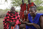 In this photo taken on Thursday, April 9, 2020, Maasai Village elder Letaari Salaash, left, sits with younger Maasai warriors at their village in Kajiado County in Kenya. The Maasai, a semi-nomadic indigenous group in Kenya and Tanzania, have been forced to halt important rituals that bring clans together due to the coronavirus, including the graduation of warriors into young men who can marry and own property. (AP Photo/Khalil Senosi)