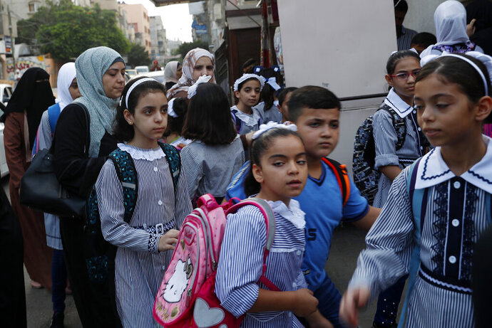 Women bring their children to the United-Nation run Elementary School on the first day of the new school year at the United-Nation run Elementary School at the Shati refugee camp in Gaza City, Saturday, Aug. 8, 2020. Schools run by both Palestinian government and the U.N. Refugee and Works Agency (UNRWA) have opened almost normally in the Gaza Strip after five months in which no cases of community transmission of the coronavirus had been recorded. (AP Photo/Adel Hana)