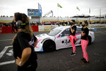 Vitarti Girl's Team mechanics Estenania Onofrio, left, Paula Salazar, center, and Victoria Pascual stand next to driver Karina Dobal before the start of their first race at the Oscar y Juan Galvez track in Buenos Aires, Argentina, Sunday, April 4, 2021. The women are part of the first entirely female team to take part in a national racing competition in Argentina. (AP Photo/Natacha Pisarenko)