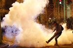 A demonstrator kicks a tear gas canister thrown by the police during a protest against President Evo Morales' reelection, in La Paz, Bolivia, Thursday, Nov. 7, 2019. The United Nations on Thursday urged Bolivia's government and opposition to restore
