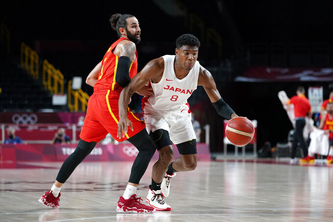 Japan's Rui Hachimura (8) drives past Spain's Rudy Fernandez (5) during a men's basketball preliminary round game at the 2020 Summer Olympics in Saitama, Japan, Monday, July 26, 2021. (AP Photo/Charlie Neibergall)