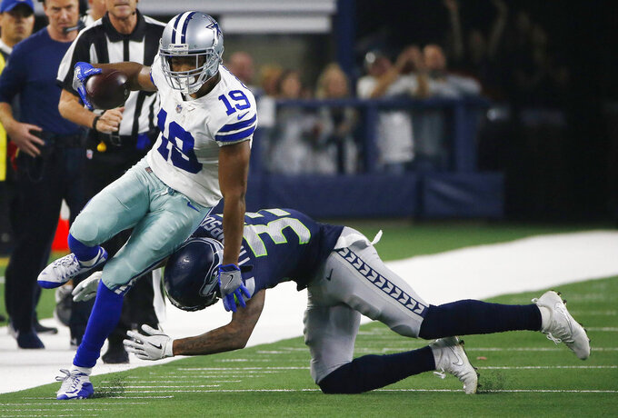 Dallas Cowboys wide receiver Amari Cooper (19) is hit by Seattle Seahawks free safety Tedric Thompson (33) during the first half of the NFC wild-card NFL football game, in Arlington, Texas, Saturday, Jan. 5, 2019. (AP Photo/Ron Jenkins)