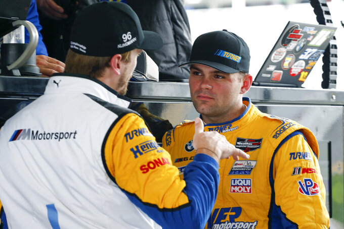 Turner Motorsports drivers Robby Foley, right, listens to fellow driver Jens Klingman in the pits during practice for the Rolex 24 hour auto race at the Daytona International Speedway, in Daytona Beach Fla., on Thursday, Jan. 23, 2020. (AP Photo/Reinhold Matay)