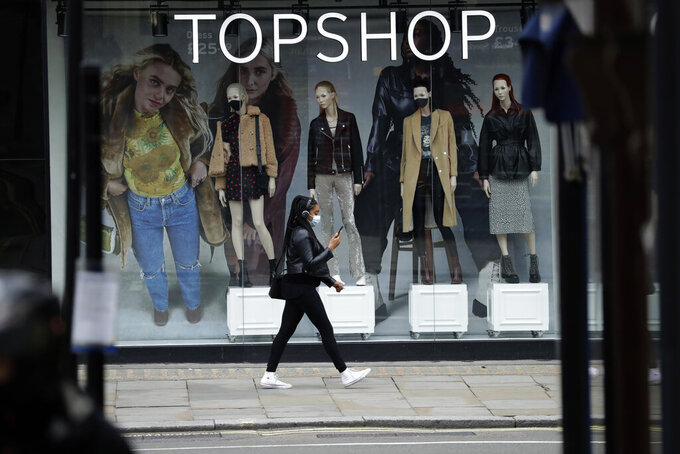 FILE - In this file photo dated Friday, Nov. 20, 2020, a woman wearing a face mask walks past mannequins wearing face masks in the window of a temporarily closed branch of the Topshop women's clothing chain during England's second coronavirus lockdown, in London.  Some 15,000 retailing jobs in Britain are in peril after Arcadia Group, owner of some of the country's best-known fashion chains like Topshop, confirmed Friday Nov. 27, 2020, that it is in talks about its future. (AP Photo/Matt Dunham, FILE)
