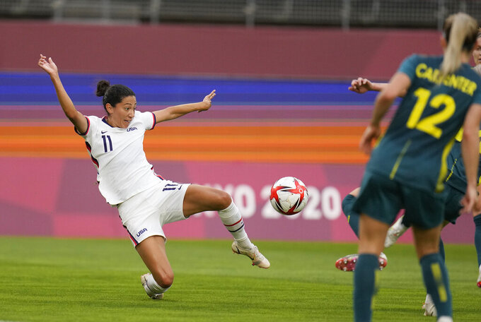 United States' Christen Press, left, goes for the ball during a women's soccer match against Australia at the 2020 Summer Olympics, Tuesday, July 27, 2021, in Kashima, Japan. (AP Photo/Fernando Vergara)