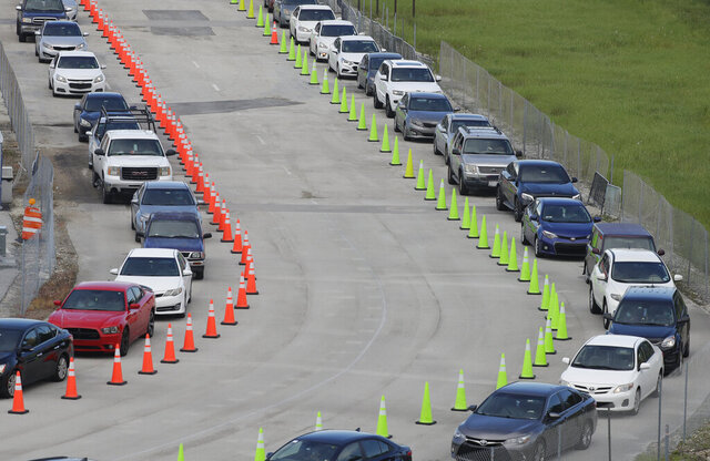 Cars wait in lines, Wednesday, Aug. 5, 2020, at a COVID-19 testing site outside Hard Rock Stadium in Miami Gardens, Fla. State officials say Florida has surpassed 500,000 coronavirus cases. Meanwhile, testing is ramping up following a temporary shutdown of some sites because of Tropical Storm Isaias. (AP Photo/Wilfredo Lee)