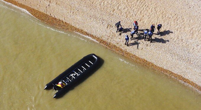 A group of people thought to be migrants are escorted to shore in Kingsdown, after being intercepted by an RNLI crew following a small boat incident in the Channel, in Kent, England, Tuesday, Sept. 7, 2021. (Gareth Fuller/PA via AP)