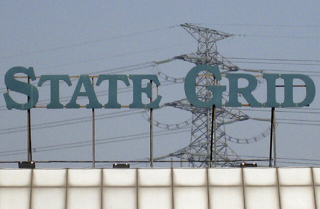 FILE - In this Feb. 28, 2009, file photo, a State Grid Corp. sign is seen above its training center in Beijing. The Chinese state-owned utility said Tuesday, Dec. 17, 2019, it has bought 49% of the power distribution grid in the Gulf nation of Oman. State Grid Corp. described the purchase as part of China's multibillion-dollar Belt and Road initiative to build trade-related infrastructure across Asia to Europe. (AP Photo/Greg Baker, File)