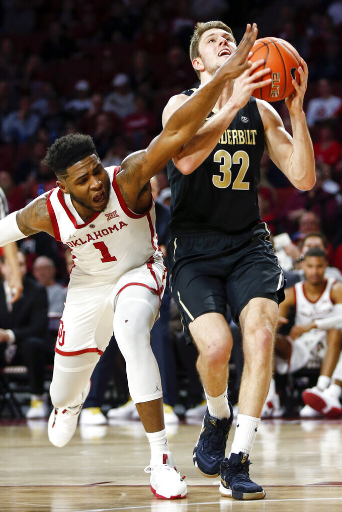 Vanderbilt's Matt Ryan (32) prepares to shoot as Oklahoma's Rashard Odomes (1) defends during the first half of an NCAA college basketball game in Norman, Okla., Saturday, Jan. 26, 2019. (Nate Billings/The Oklahoman via AP)