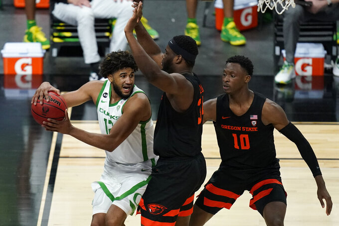 Oregon's LJ Figueroa (12) passes around Oregon State's Rodrigue Andela, center, and Warith Alatishe (10) during the second half of an NCAA college basketball game in the semifinal round of the Pac-12 men's tournament Friday, March 12, 2021, in Las Vegas. (AP Photo/John Locher)