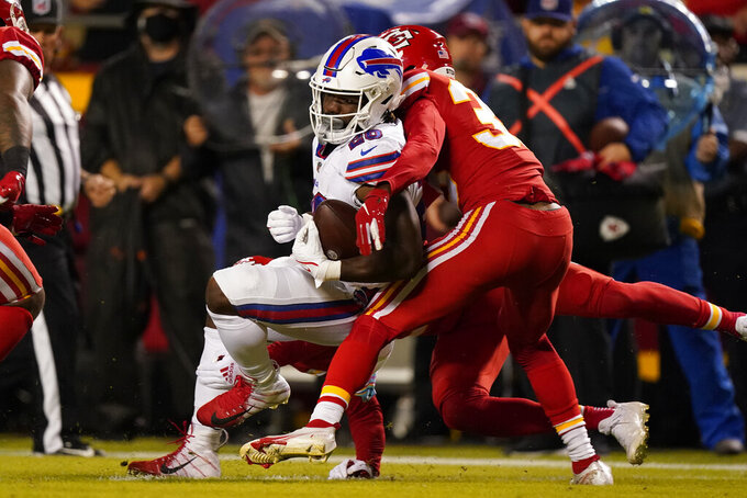 Buffalo Bills running back Zack Moss, left, struggles for yardage as Kansas City Chiefs cornerback L'Jarius Sneed, right, defends during the first half of an NFL football game Sunday, Oct. 10, 2021, in Kansas City, Mo. (AP Photo/Charlie Riedel)