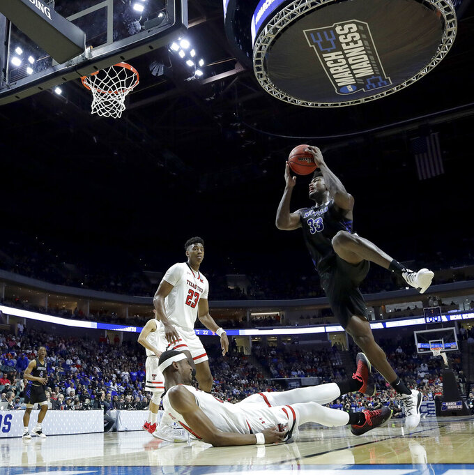 Buffalo's Nick Perkins (33) fouls Texas Tech's Tariq Owens as he puts up a shot during the first half of a second round men's college basketball game in the NCAA Tournament Sunday, March 24, 2019, in Tulsa, Okla. (AP Photo/Charlie Riedel)