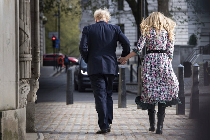 Britain's Prime Minister Boris Johnson and his fiancee Carrie Symonds leave after casting their vote in the local and London Mayoral election, at Methodist Central Hall, in central London, Thursday May 6, 2021. Polling stations across Britain opened Thursday in what are considered to be the biggest-ever set of elections outside a general election and which could have huge repercussion for the future of the United Kingdom. (Stefan Rousseau/PA via AP)