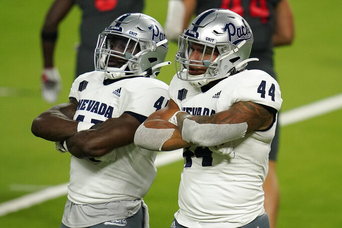Nevada linebacker Trevor Price, left, and defensive end Daniel Grzesiak (44) celebrate after a play against UNLV during the second half of an NCAA college football game Saturday, Oct. 31, 2020, in Las Vegas. (AP Photo/John Locher)