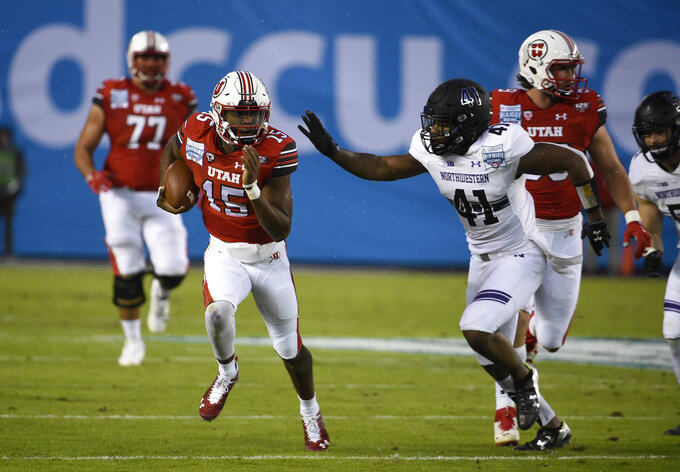 Utah quarterback Jason Shelley (15) runs away from Northwestern safety Jared McGee (41) on his way to a first down during the first half of the Holiday Bowl NCAA college football game against Utah, Monday, Dec. 31, 2018, in San Diego. (AP Photo/Denis Poroy)