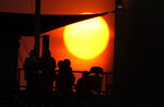 The sun sets as fans wander the main concourse of Coors Field in the fourth inning of a baseball game between the Colorado Rockies and the San Diego Padres on Tuesday, June 15, 2021, in Denver. (AP Photo/David Zalubowski)